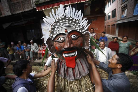 Nepalese people make an effigy of Ghanta Karna, symbolic of demons, during a festival celebrated after paddy planting in Bhaktapur, outskirts of Katmandu, Nepal.