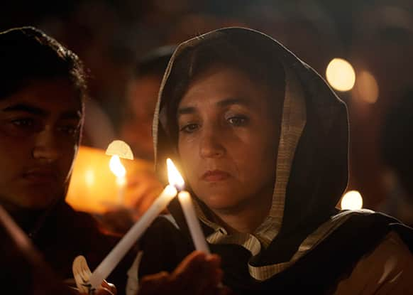 People light each others candles during a candlelight vigil at the Sikh Temple of Wisconsin to mark the one-year anniversary of the shooting rampage that left six dead, in Oak Creek, Wis.