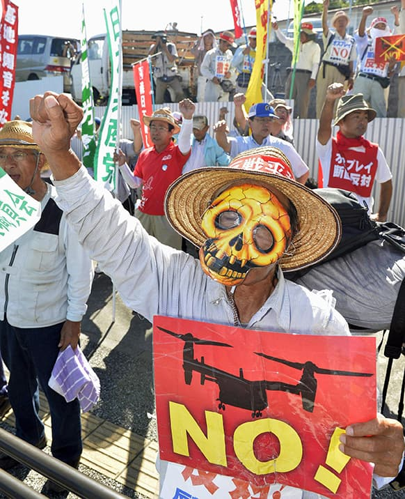 Protesters chant slogans against Monday`s accident of a US military helicopter crash and planned additional deployment of Osprey transport aircraft in front of a gate to US.