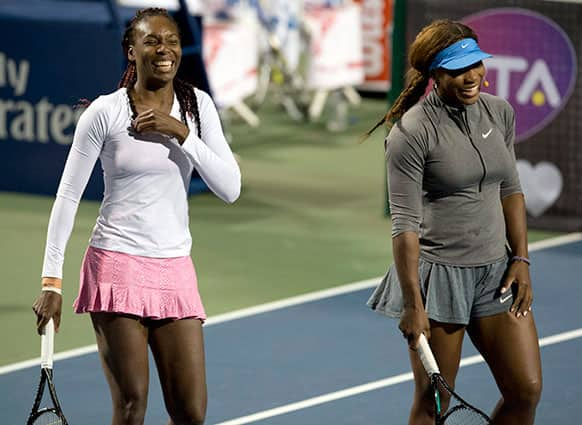 Venus Williams and Serena Williams laugh during an exhibition doubles match during Rogers Cup women`s tennis action in Toronto.