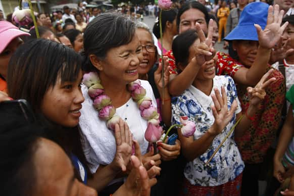 A Lawmaker of National Rescue Party Mu Sochua, center, poses for photographs with villagers during her visit to Boeung Kak lake, in Phnom Penh, Cambodia.