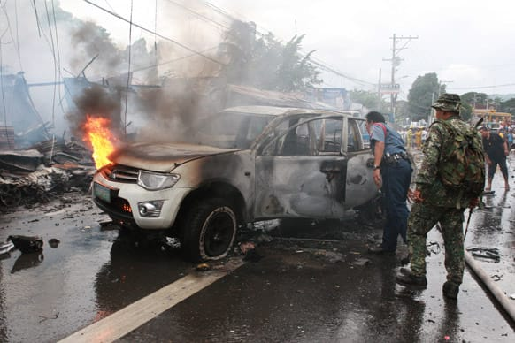 Police and military personnel inspect a burnt vehicle after a powerful bomb exploded in Cotabato city, southern Philippines.