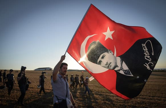 A man walks with a national flag with an image of Turkey`s founder Kemal Ataturk outside the Silivri jail complex outside the Silivri jail complex in Silivri, Turkey.