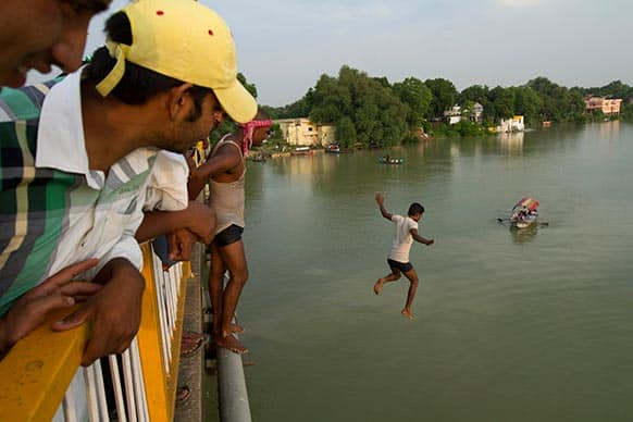 A man jumps to swim from a bridge across the River Ganges which is flooded after heavy monsoon rains in Allahabad.