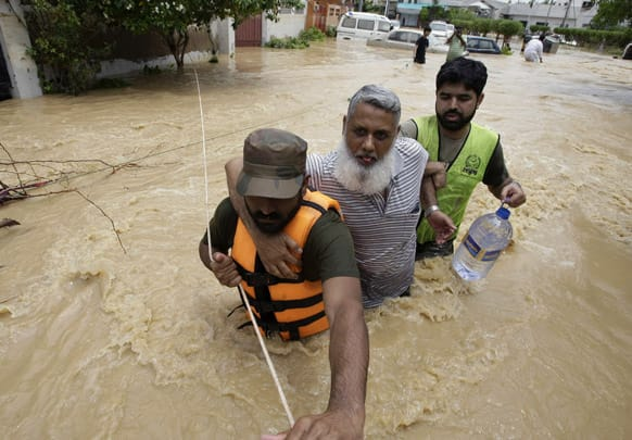 Pakistani soldiers rescue a resident from an area flooded by heavy rains on the outskirts of Karachi, Pakistan.