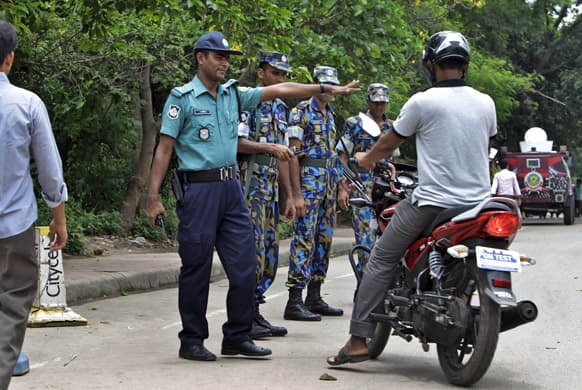 Bangladeshi police stop a motorist for checking in front of the US embassy building that remained closed due to security threat in Dhaka.