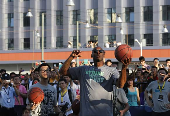 NBA star Kobe Bryant throws a ball during a meeting with fans in China`s southern city of Shenzhen.