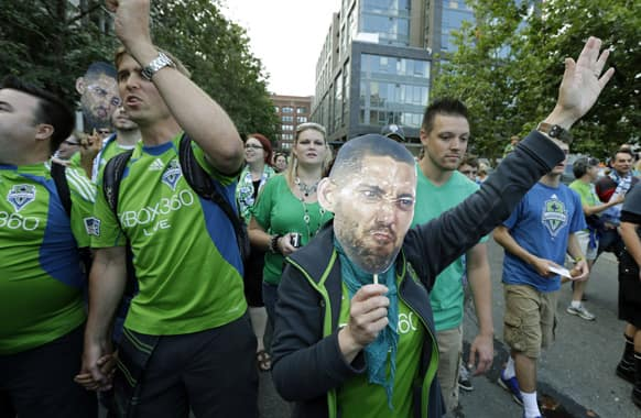 Seattle Sounders fans carry photos of Clint Dempsey, captain of the US Mens National Team, as they take part in the traditional