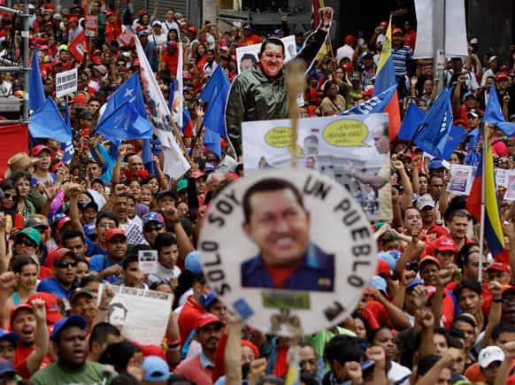 Posters and cutouts of the late Venezuelan leader Hugo Chavez dot the crowd as President Nicolas Maduro delivers a speech during a protest against corruption in Caracas, Venezuela.