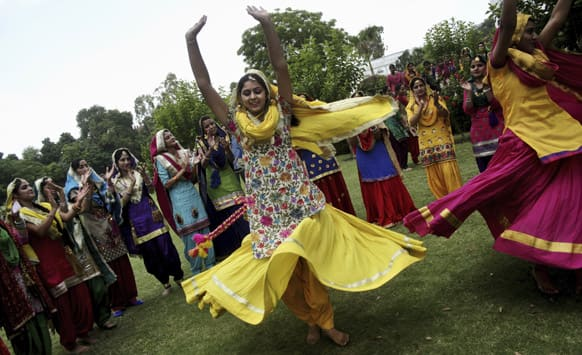College students perform a Punjab folk dance to celebrate the Teej festival in Amritsar.