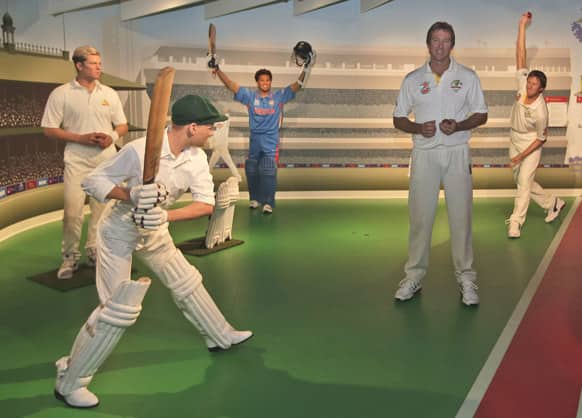 Former Australian cricket player Glenn McGrath, 2nd right, poses among cricket legends from left, Shane Warn, Donald Bradman, Sachin Tendulkar and a wax statue of himself, right, at Madame Tussauds in Sydney, Australia.