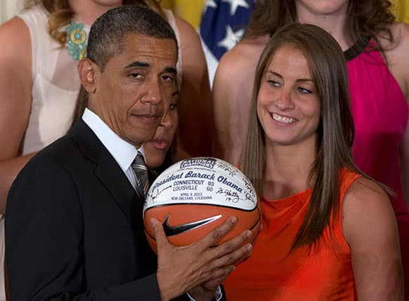 University of Connecticut Huskies basketball guard Caroline Doty looks at President Barack Obama as he shows the signed basketball she just gave him during a ceremony in the East Room of the White House in Washington.