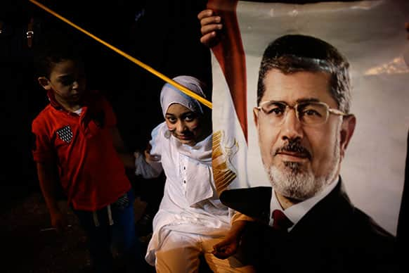 An Egyptian child stands next to poster of the Egypt`s ousted President Mohammed Morsi outside Rabaah al-Adawiya mosque, where supporters have installed a camp and hold daily rallies at Nasr City, in Cairo, Egypt.