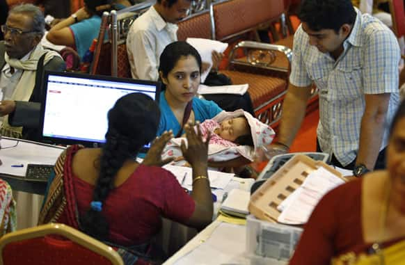 A taxpayer holds her baby as she listens to an official before filing her income returns for the previous financial year at a special counter set up by the Income Tax department in Bangalore.