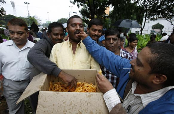 People celebrate by distributing sweets after India`s ruling coalition endorsed creating a new state in southern India, in Hyderabad.