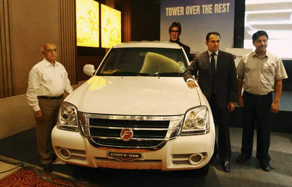 President of corporate sales & marketing of Force Motors Limited NK Rattan, left, Managing Director of Force Motors Limited Prasan Firodia second from left, and principal dealer Ramesh Puri pose for a photo during the launch of the SX variant of the Force One SUV in New Delhi.