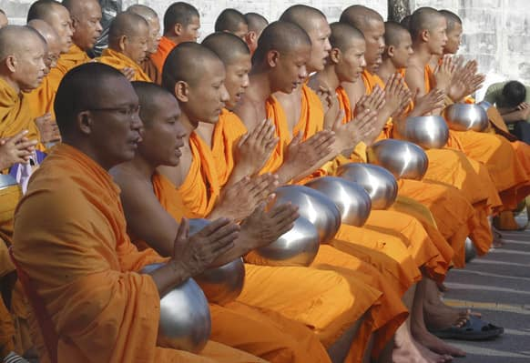 Buddhist monks pray during a morning alms offering ceremony held at the Muslim dominated province of Yala, southern Thailand.