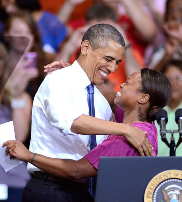 President Barack Obama hugs Amazon employee Lydia Flanders after she introduced him, at the Amazon fulfillment center in Chattanooga, Tenn.