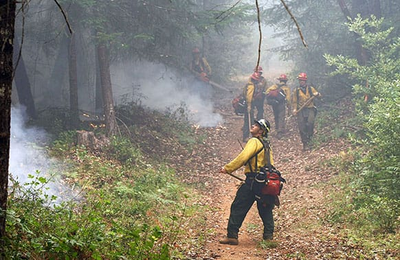 Oregon Woods crew leader Chuck Watkins, front, monitors a small section of the Douglas Complex Fire as his crew clears a break line outside Glendale, Ore.