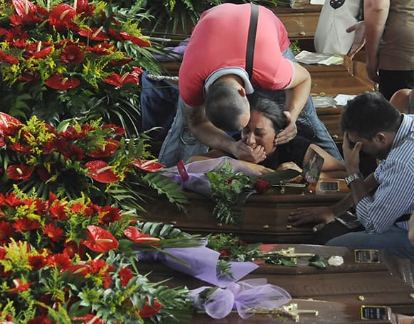People mourn their loved ones amongst the coffins of some of the victims of Sunday`s bus crash prior to the start of their funeral service, in Pozzuoli, near Naples, southern Italy.