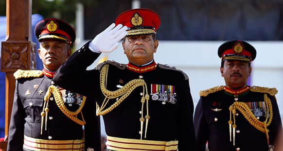 Sri Lankan army commander Lt. Gen. Jagath Jayasuriya, center, salutes as the next Army Commander Major Gen. Daya Ratnayake, left, and Major Gen. Jagath Dias watch a military parade in Colombo, Sri Lanka.