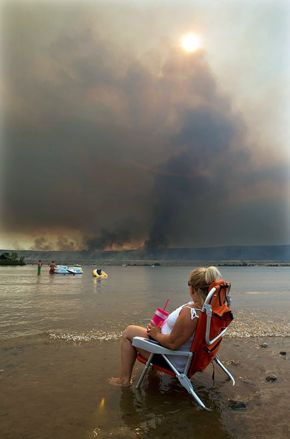 Jody Erickson, of Kent, Wash., watches the Colockum Tarps fire from her beach chair, while sitting on the bank of the Columbia River at the Crescent Bar Resort south of Malaga, Wash.