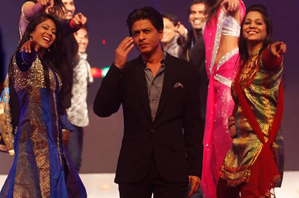 Bollywood star Shah Rukh Khan, center, performs during an event to promote his upcoming movie