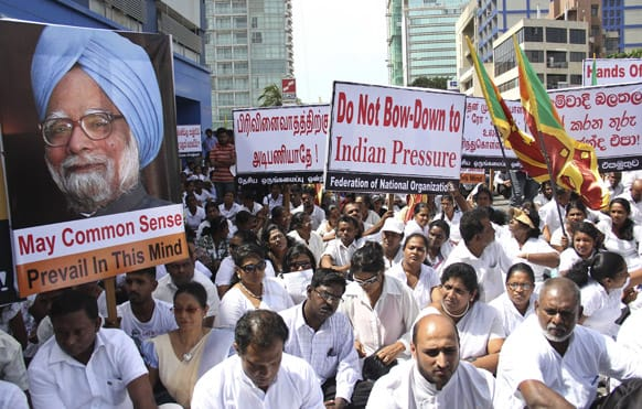 A protestor holds a placard with a photograph of Indian Prime Minister Manmohan Singh during a protest by Federation of National Organizations, a collective of nationalistic groups, out side the Indian High Commission in Colombo, Sri Lanka.