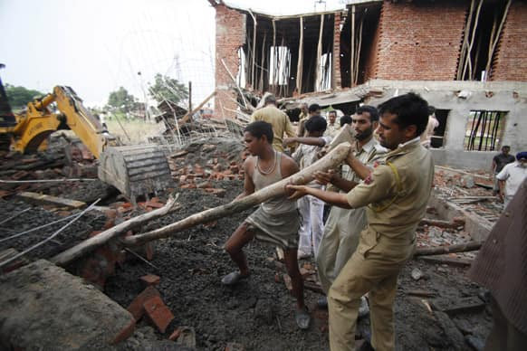 Rescue workers search through the debris of an under construction building, which collapsed on the outskirts of Jammu.