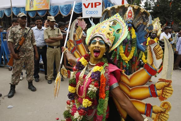 Security men watch artists dressed like Hindu goddess Kali perform during Bonalu festival in Hyderabad.