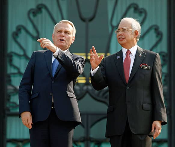 France`s Prime Minister Jean-Marc Ayrault, left, talks with Malaysian Prime Minister Najib Razak during a welcome ceremony in Putrajaya, Malaysia. Ayrault is on a two-day official visit to Malaysia.