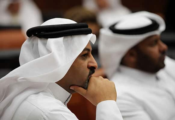 Bahraini lawmakers Khaled Abdel A`al, left, and Osama al-Tamimi, right, listen during a special session of parliament to discuss how to handle the uprising in the Gulf island kingdom, convened in Manama, Bahrain.