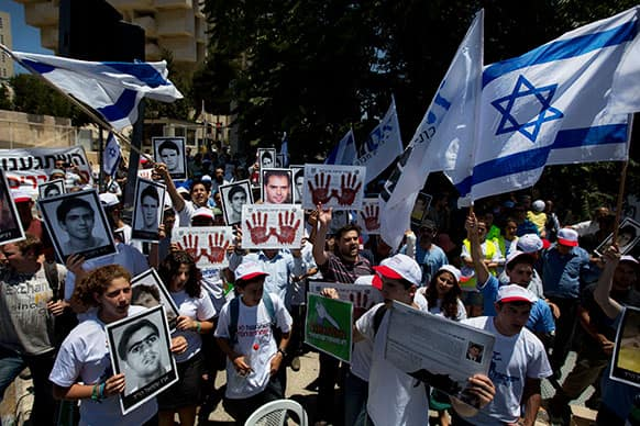 Israeli protesters hold flags, pictures of Israelis who they say were killed by Palestinians, and posters with bloody hands and Hebrew writing that reads,