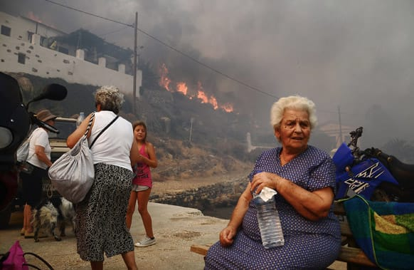 Inhabitants and holidaymakers evacuate the village of Megalo Livadi on Greece`s Aegean island of Serifos as a wildfire rages.