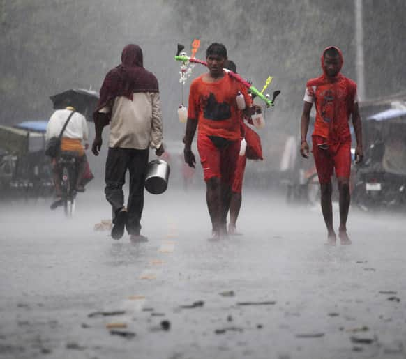 Hindu pilgrims, known as Kanwarias, walk in the rain on the outskirts of Allahabad.