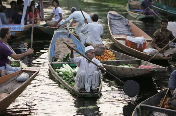 A Kashmiri man paddles his boat loaded with vegetables at the floating vegetable market on Dal Lake in Srinagar.