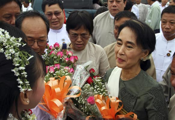 Myanmar opposition leader Aung San Suu Kyi receives flowers from her supporters upon arrival to attend the opening ceremony of a central library at Kaw Hmu township in Yangon, Myanmar.