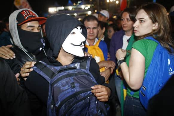 Anti-government demonstrators, left, walk past pilgrims attending the Way of the Cross service on the Copacabana beachfront, in Rio de Janeiro, Brazil.