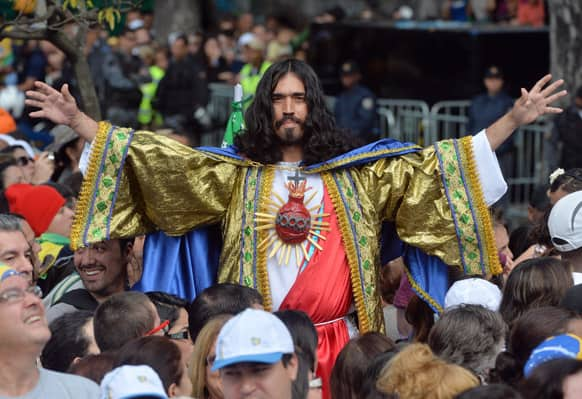 A man dressed as Jesus Christ poses for a photo as he with others for Pope`s Francis` to give Angelus noon prayer at the Sao Joaquim Palace in Rio de Janeiro, Brazil.