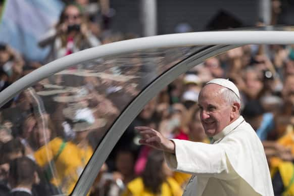 Pope Francis waves to people from his popemobile in the Gloria neighborhood as he travels to the archbishops`s palace where he`ll hold a series of meetings and public noon prayer in Rio de Janeiro, Brazil.
