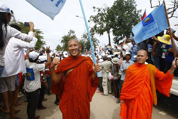 Buddhist monks carry the opposition Cambodia National Rescue Party flags during a final campaign rally in Phnom Penh, Cambodia.