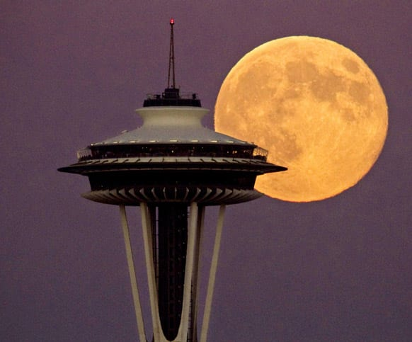 A full moon rises besides the Space Needle, in Seattle. This view is from the Ursula Judkins Viewpoint, part of Smith Cove Park, in Magnolia, Wash.