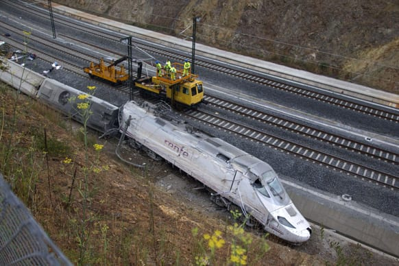 Rail workers are seen next to derailed cars at the site of a train accident in Santiago de Compostela, Spain.