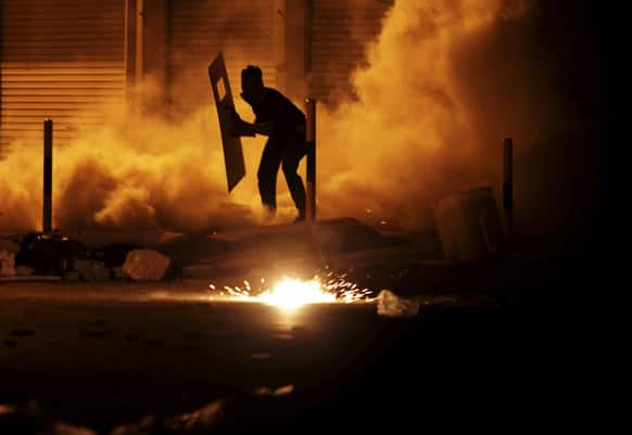 A Bahraini anti-government protester carrying a makeshift shield reacts to tear gas fired by riot police during clashes in Diraz, Bahrain.