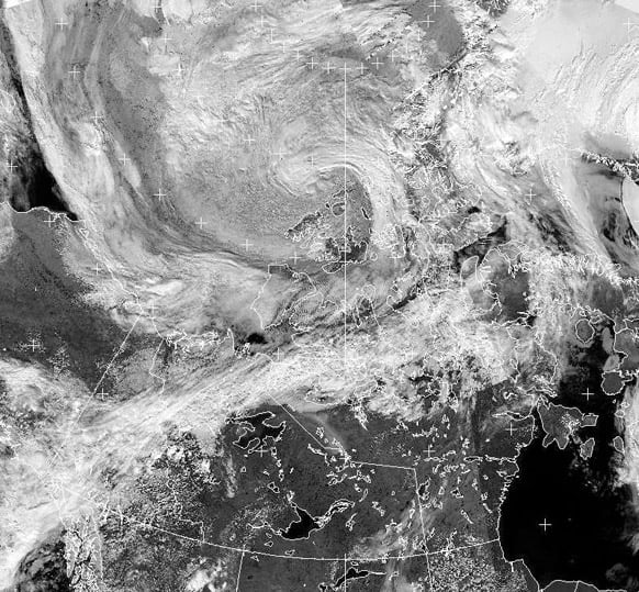 A cyclone, upper center, forms over the Canadian Arctic, seen in an Environment Canada/NOAA satellite image taken at 3:42 p.m. EDT.