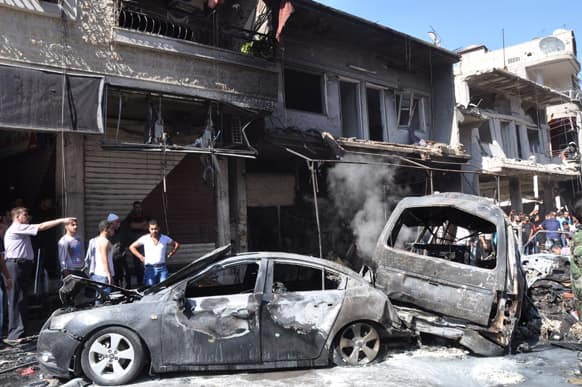 This photo released by the Syrian official news agency SANA, Syrian citizens gather near damaged cars that were burned after a car bomb exploded in the suburb of Jaramana, Damascus, Syria.
