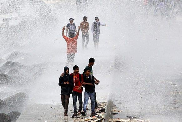 Indians enjoy high tide waves on the Arabian Sea coast during monsoon rains in Mumbai.