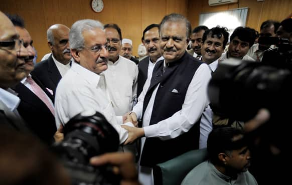 Mamnoon Hussain, center right, a candidate from ruling party Pakistan Muslim League-N shakes hands with Raza Rabbani, a candidate from opposition party Pakistan People Party after submitting their nomination papers for upcoming presidential election in Islamabad.