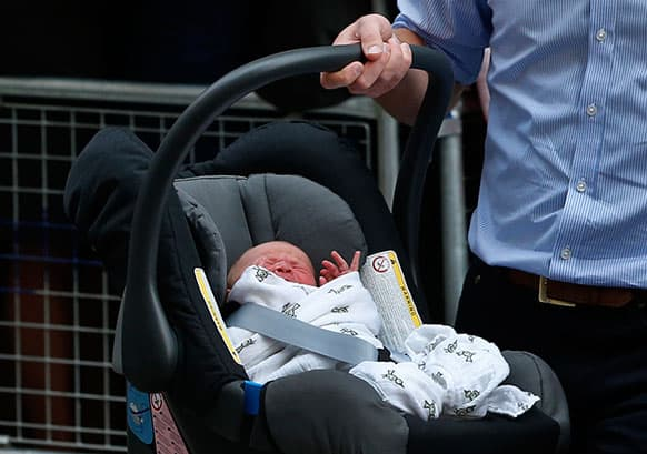 Britain`s Prince William carries his son the Prince of Cambridge into a car outside St. Mary`s Hospital exclusive Lindo Wing in London, where his wife, Kate, the Duchess gave birth on Monday.