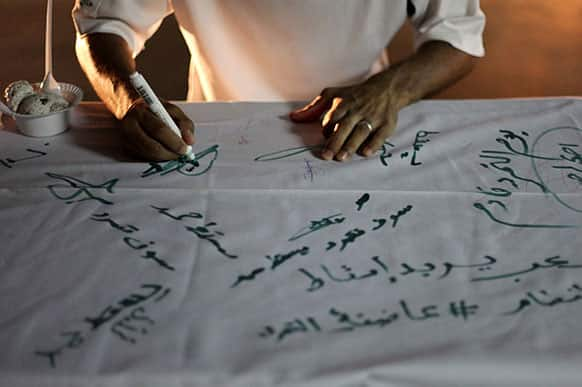 A Bahraini anti-government protester signs a petition, set up in a street in the western village of Malkiya, Bahrain.